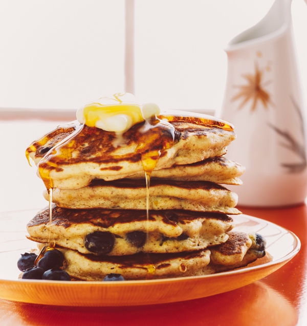 pancakes and butter drizzled syrup with blueberries breakfast