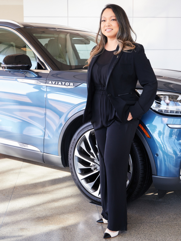 stylish woman in black pants, jacket, and blouse standing next to aviator car