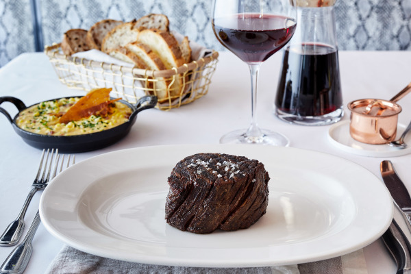 filet mignon on plate with glass of wine and basket of bread