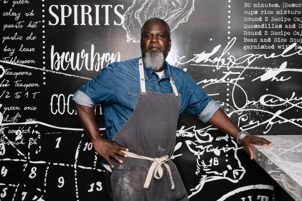 chef with white beard wearing jean shirt and grey apron has hand on marble counter to the side