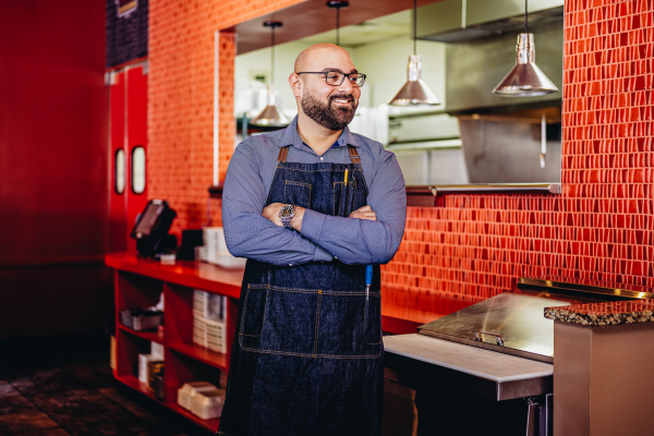 chef at andiamo-dearborn restaurant with arms folded in front of kitchen