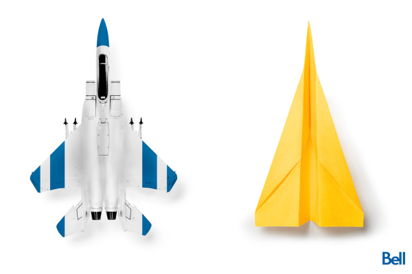 overhead blue and white fighter jet next to yellow paper airplane
