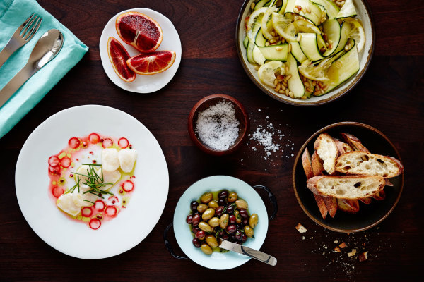 overhead shot of a table holding bowls of olives, zucchini, salt, scallops, blood orange, and crusty bread