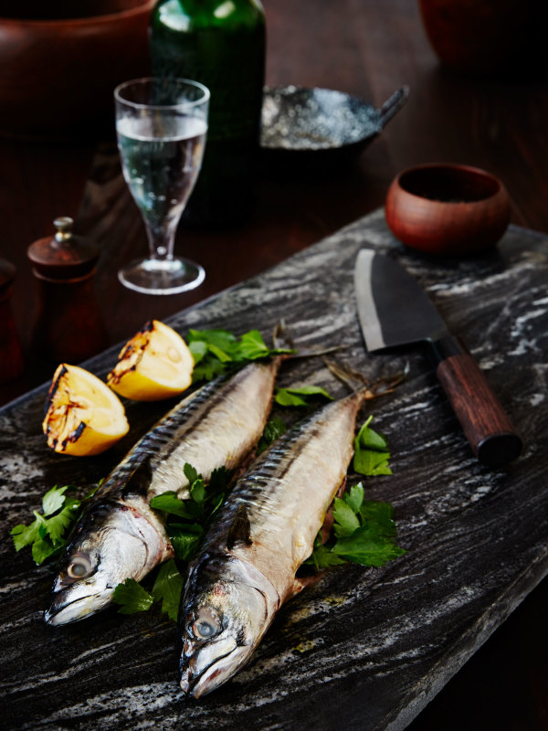 two broiled fish next to grilled lemon and knife on marble cutting board
