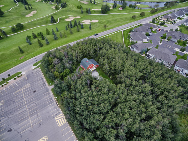 aerial view of red farmhouse in wooded area next to parking lot, houses, and golf course