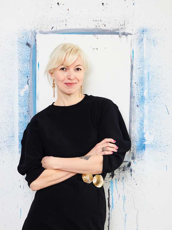 painter julia dault with her arms folded leaning against a wall with a blue painted frame