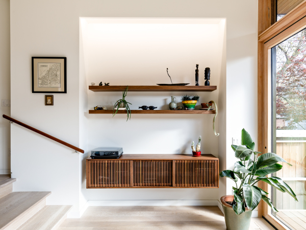landing with wooden shelves and leafy plant between stairs and window leading to backyard
