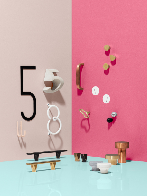 various drawer handles arranged on a light blue floor with pink walls