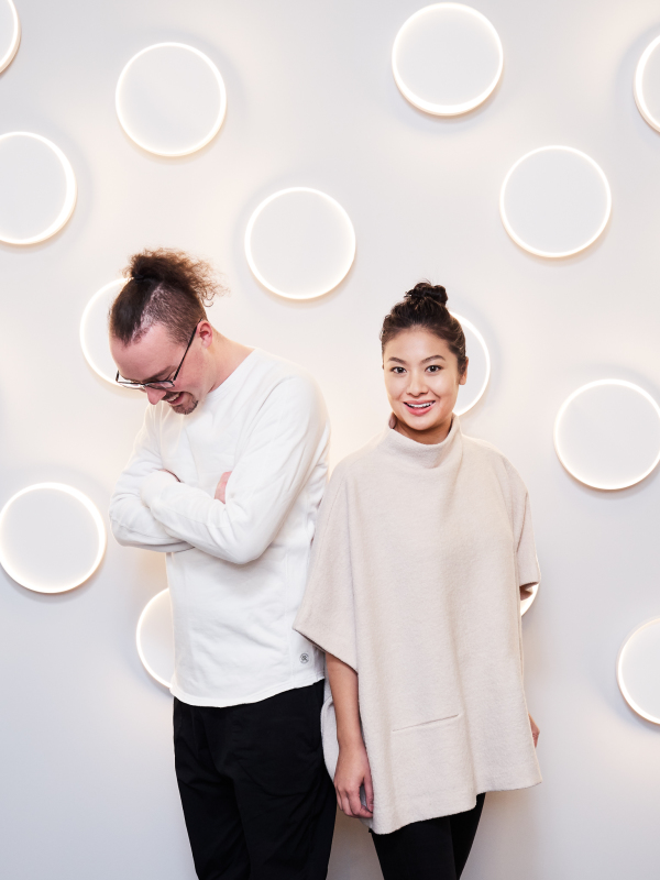 two designers standing in front of wall with illuminated circles