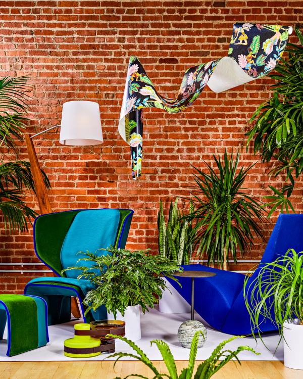 two modern blue chairs surrounded by plants against a brick wall