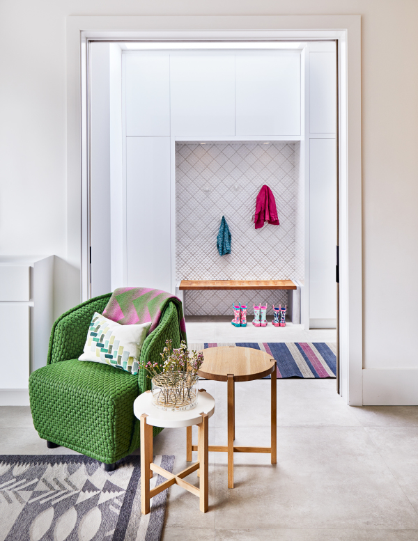 two side tables next to a comfortable green chair draped in pink and green blanket