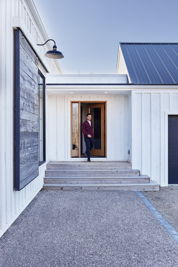 Man walking out door of white vertically panelled house with a blue roof