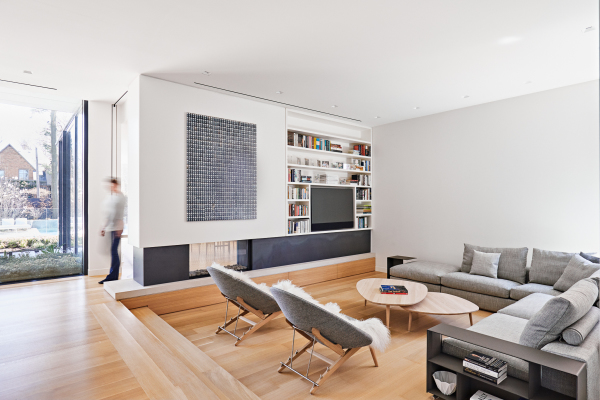 living room with grey chairs and sofa forming u shape in sunken wooden space. TV surrounded by a bookshelf in the corner.