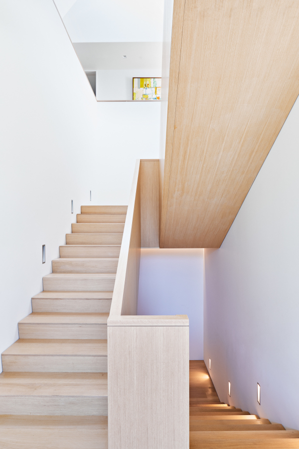 clean wooden staircase in upscale home ascending on the left descending on the right