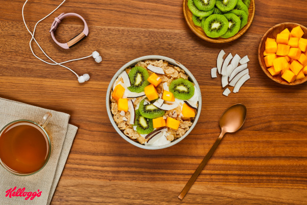 wooden table with bowl of cereal with coconut, mango, and kiwi. A fitbit watch rests beside earbuds and cup of hot tea