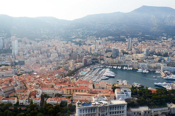 aerial view of port in monaco with clay coloured buildings before mountain range