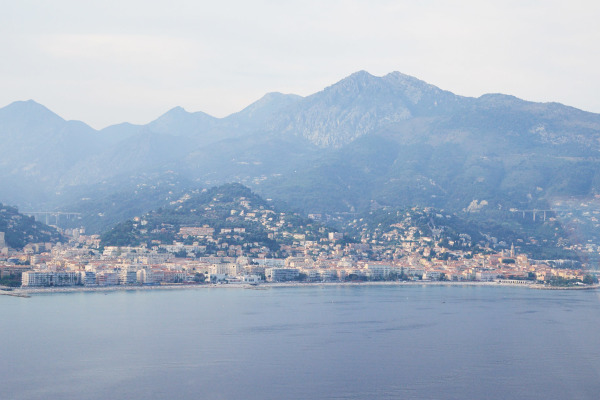 aerial view from across a body of water of a village in monaco before a mountain range