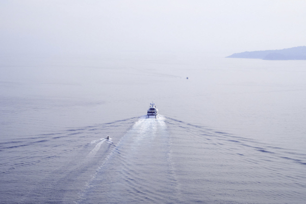 a high view of single boat driving in the distance