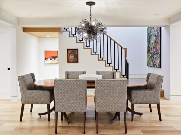 staircase with iron and wood bannister descends in the background of the dining area featuring 6 cushioned brown chairs and a brown table