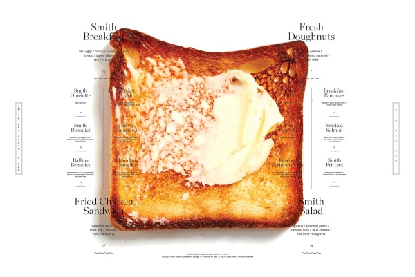 A well done piece of toast with slightly burnt corners and the breakfast menu for the Smith Restaurant
