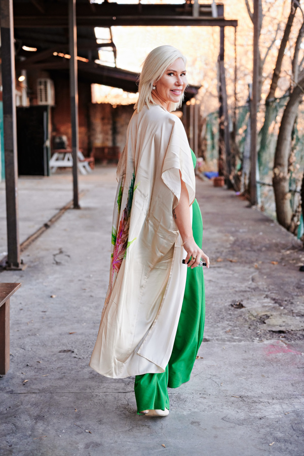 Blond woman with vaporizer in green dress walking away but looking back