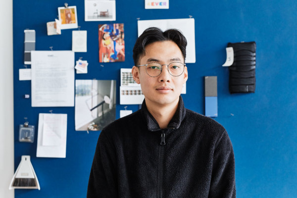 man in glasses posing for company portrait against wall covered in notes