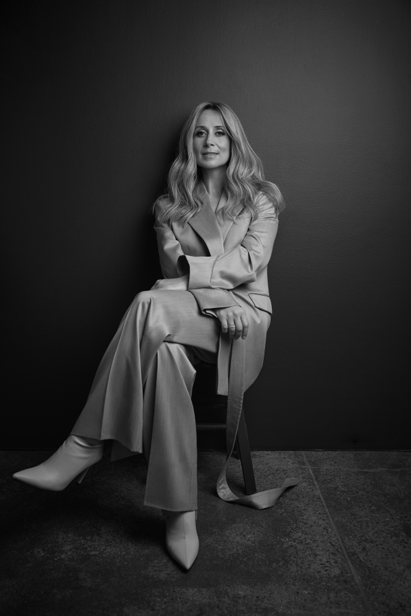 Lara Fabian sitting on a chair with her legs crossed